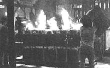 Foundry employees pour iron simultaneously.